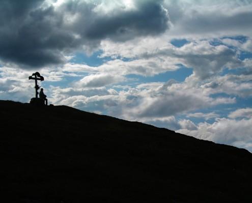Wanderer am Gipfelkreuz des Laubenstein